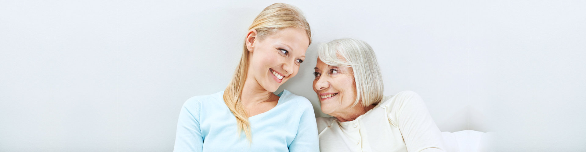 caregiver and elderly woman are smiling